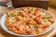 Pizza with topping  pork sausage, Italian sausage, pepperoni, ha. M, bacon,  mozzarella cheese,onion, capsicum, mushroom and pineapple Royalty Free Stock Photos