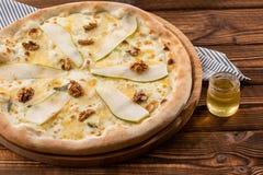 Pizza tradicional com pera, porcas e queijo azul em um fundo de madeira Fim acima Vista superior foto de stock royalty free