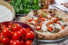 Pizza tradicional italiana con la mozzarella, la salchicha, el tomate y p Imagen de archivo libre de regalías