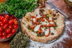 Pizza tradicional italiana con la mozzarella, la salchicha, el tomate y p Fotografía de archivo