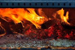 Pizza in a traditional italian fire-place, blazing fire Stock Photos
