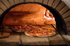 Pizza in traditional oven Stock Images