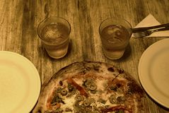 Pizza with two glasses in a wood background. Picture of Pizza with two glasses in a wood background royalty free stock photo