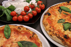 Pizza. Two pizzas and some ingredients: tomatoes and mozzarella Royalty Free Stock Photos