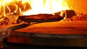 Pizza in un forno del fuoco di legno archivi video
