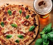 Pizza und Bier auf Holztisch lizenzfreie stockfotografie