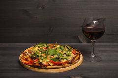 Pizza und ein Glas Rotwein auf hölzernem Hintergrund Stockfotografie