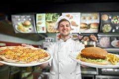 Pizza und haumburger mit freier Kartoffel in den Händen des männlichen Kochs lizenzfreie stockbilder