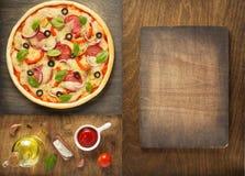 Pizza und Lebensmittelinhaltsstoffe am Holztisch lizenzfreie stockbilder