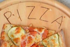 Pizza und schriftliches Pizzawort Lizenzfreie Stockfotografie