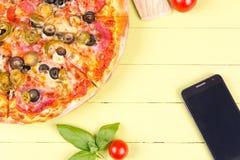 Pizza und Telefon auf Holztisch Stockfotos