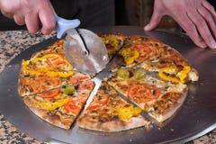 Pizza végétarienne de Slicing Fresh Baked de Baker avec le coupeur de pizza Image stock