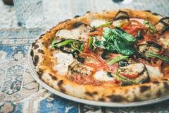 Pizza végétarienne fraîchement cuite au four avec le basilic au-dessus du fond oriental de tuile Photo stock