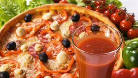 Pizza with vegetables and glass of tomato juice Stock Images