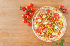 Pizza with vegetables and ham on wooden table - Top view Stock Image