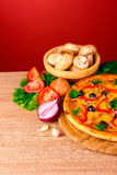 Pizza and vegetables on red Stock Photography