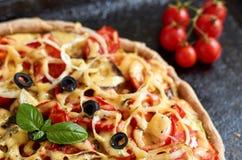 Pizza vegetariana calda con i pomodori, il peperone dolce, la cipolla, le olive nere, il formaggio e le spezie sulla fine scura n Immagini Stock Libere da Diritti