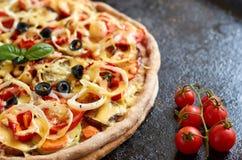 Pizza vegetariana calda con i pomodori, il peperone dolce, la cipolla, le olive nere, il formaggio e le spezie sulla fine scura n Fotografia Stock