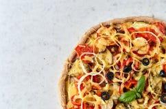 Pizza vegetariana calda con i pomodori, peperone dolce, cipolla, olive nere, formaggio, spezie sulla fine leggera del fondo su co Immagini Stock