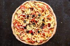 Pizza vegetariana calda con i pomodori, peperone dolce, cipolla, olive nere, formaggio, spezie sulla fine scura nera del fondo su Immagini Stock Libere da Diritti