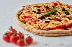 Pizza vegetariana caliente con los tomates, el paprika, la cebolla, las aceitunas negras, el queso y las especias en el cierre bl Foto de archivo libre de regalías