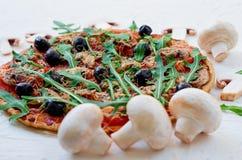 Pizza vegetariana con i funghi, pomodori, olive nere, rucola sui precedenti bianchi decorati con i funghi freschi Fotografie Stock Libere da Diritti