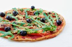 Pizza vegetariana con i funghi, pomodori, olive nere, rucola sulla tavola bianca isolata Immagini Stock Libere da Diritti