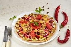 Pizza vegetariana con los tomates, el paprika, la cebolla, las aceitunas verdes, el queso y las especias en el cierre blanco del  Imagen de archivo libre de regalías