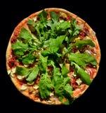 Pizza vegetariana deliciosa hecha en casa rústica con arugula sobre el fondo negro, visión superior Foto de archivo libre de regalías
