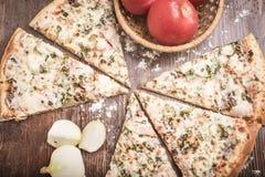 Pizza, vita lökar och nya tomater på en brun träbakgrund Arkivfoton