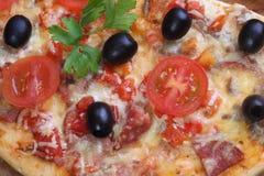 Pizza von einer Salami, von einem Schinken und von den Tomaten auf einem Holztisch Lizenzfreie Stockbilder