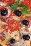 Pizza von einer Salami, von einem Schinken und von den Tomaten auf einem Holztisch Lizenzfreies Stockbild