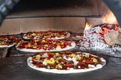 Pizza w łupka piekarniku z płomieniem behind zdjęcie stock