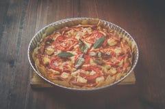 Pizza w metalu talerzu na drewno stole Rocznika tonowanie Obraz Stock