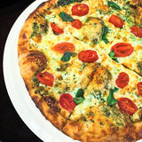 Pizza with white cheese, tomatoes and herbs Royalty Free Stock Photography