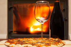 Pizza and wine at the fireplace Royalty Free Stock Photography