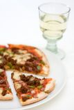 Pizza and wine glass over white. A pizza with spiced beef, green peppers and red onion on a white plate with a slice cut out and glass of white wine in the Royalty Free Stock Photo