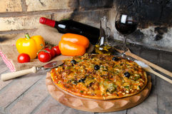 Pizza with wine and some ingredients on a firebricks background. Composition with a pizza, wine and some ingredients on a firebricks background Stock Image