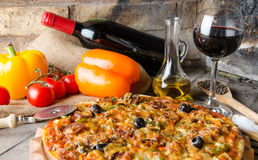 Pizza with wine and some ingredients on a firebricks background. Composition with a pizza, wine and some ingredients on a firebricks background Royalty Free Stock Photos