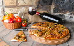 Pizza with wine and some ingredients on a firebricks background. Composition with a pizza, wine and some ingredients on a firebricks background Royalty Free Stock Image