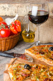 Pizza with wine and some ingredients on a firebricks background. Composition with a pizza, wine and some ingredients on a firebricks background Stock Photo