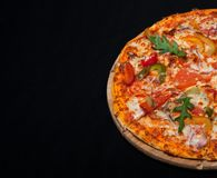 Pizza on a wood board with a copy of the place on a black background Stock Images