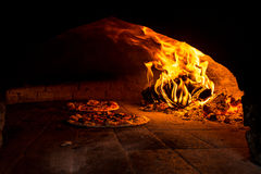 Pizza in a wood burning oven Royalty Free Stock Images