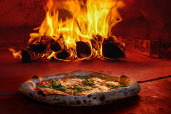 Pizza in wood fired oven with open fire. Traditional wood fired oven baked pizza tomato mozzarella basil Royalty Free Stock Photo