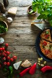 Pizza on wood with ingredients stock photography