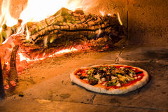 Pizza in a wood oven. Pizza in a traditional Italian stone oven Royalty Free Stock Photos