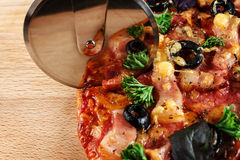 Pizza on wooden board with knife Stock Photos