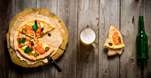 Pizza on wooden circle, beer, and a bottle on a wooden table. Royalty Free Stock Photography