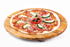 Pizza on wooden plate. Freshly prepared pizza on wooden plate ready to cook, white background stock photos