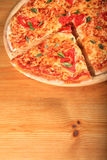 Pizza on a wooden plate Stock Photos